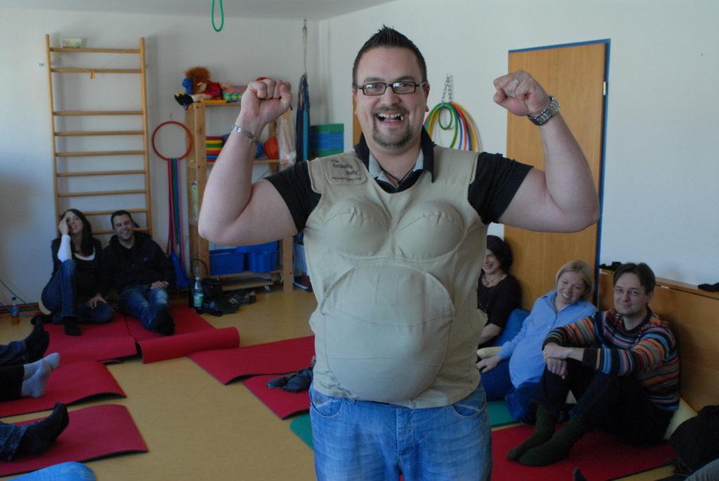 """Das Bild zeigt einen Vater, der im Geburtsvorbereitungskurs von Anja Lehnertz den """"Empty Belly"""" trägt - also eine Art Rucksack vor dem Bauch, der einen Schwangerschaftsbauch mit entsprechendem Gewicht simuliert."""